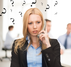 bright picture of confused woman with phone in office